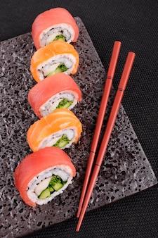 Zalm tonijn sushi roll met eetstokjes op een zwarte plaat