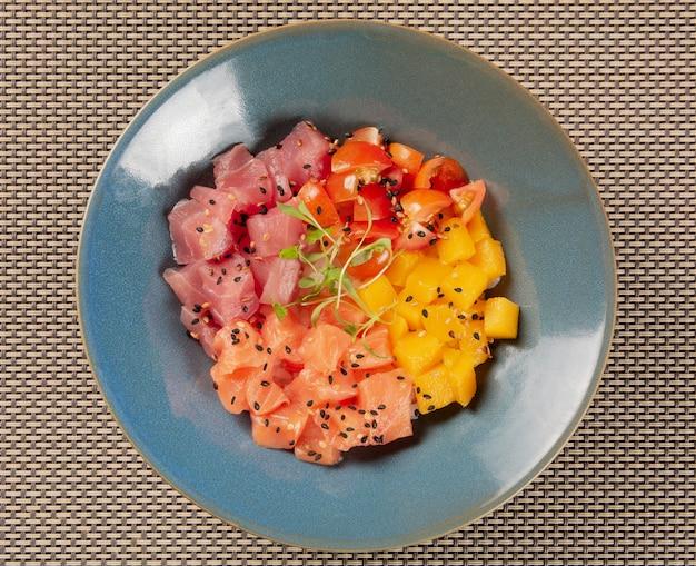 Zalm, tonijn, tomaat en mango porren in een blauwe kom