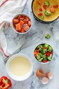 Zalmfilet, broccoli en rode peper in kom, meng melk en eieren, scherp deeg op een witte lijst