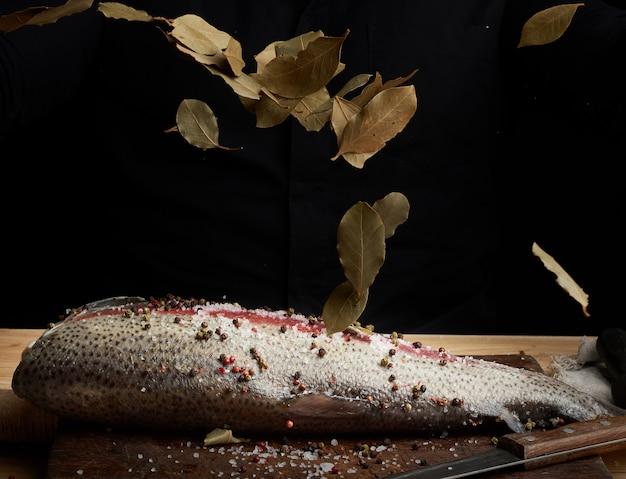 Zalmfilet zonder kop op een houten bord dat met bladeren van droge laurierbladeren wordt bestrooid