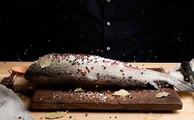 Zalmfilet zonder kop op een houten plank bestrooid met grote witte peper en zout