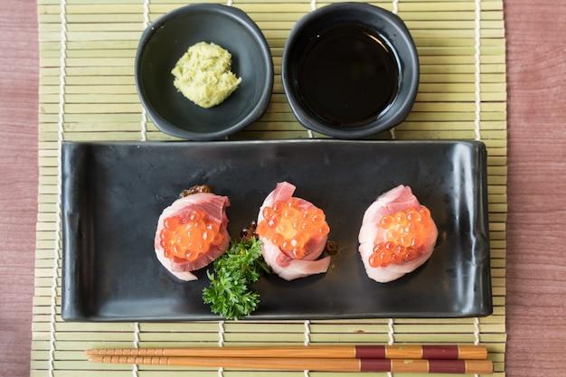 Zalmkuiten op hamachi-sushi op zwarte plaat samen met japanse saus