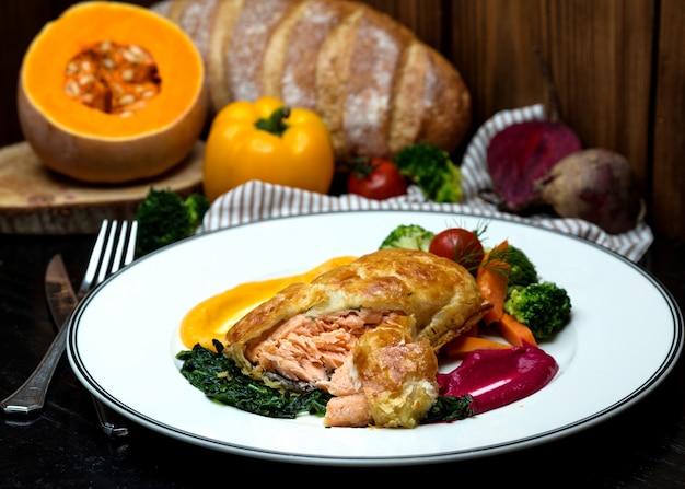 Zalmpastei geserveerd met geroosterde kruiden, groenten en zure saus