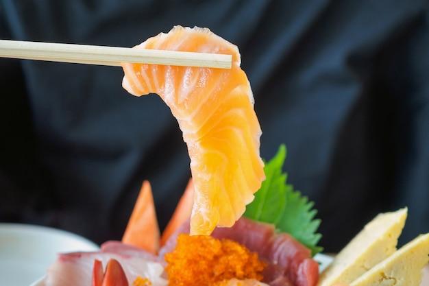 Zalmplak in eetstokjes, die sashimi rijstkom eten chirashi don japans voedsel