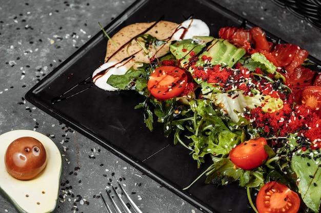 Zalmsalade gravlax gerookte zalmsalade met gemengde greens cherrytomaatjes avocado zwarte olijven