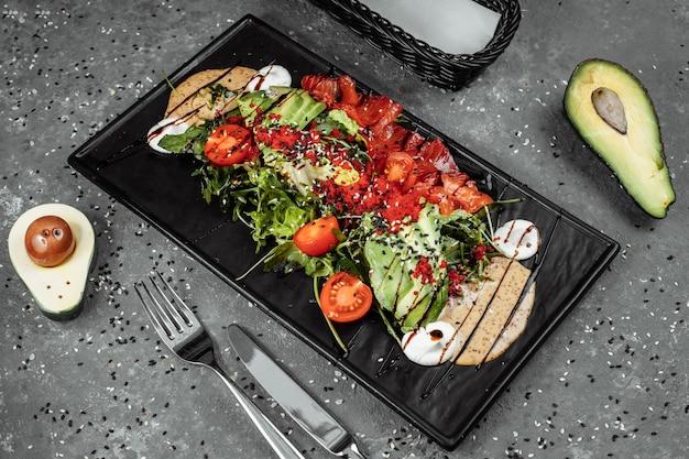Zalmsalade gravlax. salade van gerookte zalm, met gemengde groenten, cherrytomaatjes, avocado, zwarte olijven, wortelen, spruitjes, komkommer en limoen. heerlijk gezond eten
