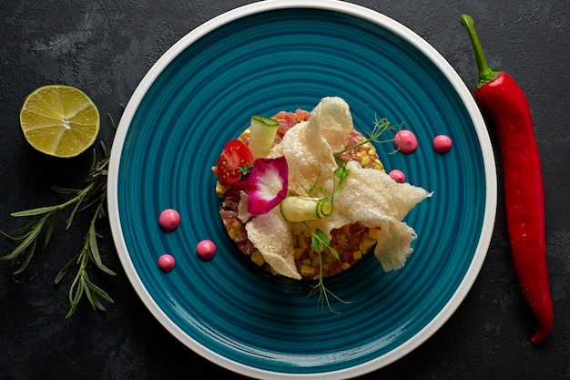 Zalmsalade met avocado, op een blauw gestreept bord, met limoen, met chilipepers, eetbare bloemen, rozemarijn en frietjes