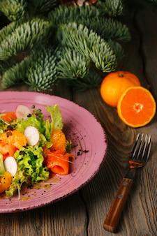 Zalmsalade met sinaasappel, guacamole en glas witte wijn op kerstmisdecoratie.