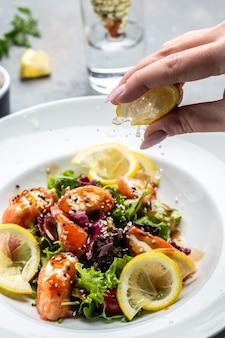 Zalmsalade met sla greens en citroen. spatten van citroensap, voedsel recept achtergrond. detailopname