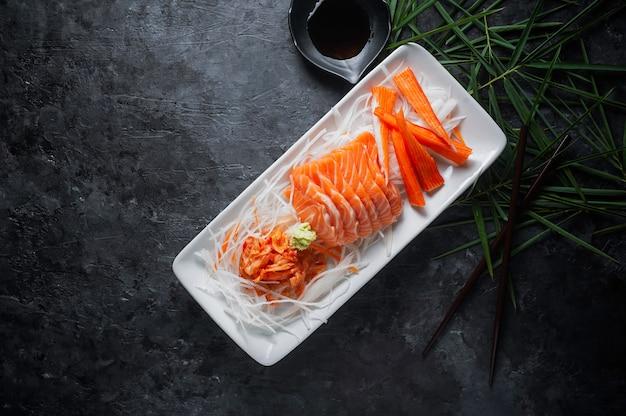 Zalmsashimi en imitatie krabstok in japanse stijl met kimchi, wasabi.