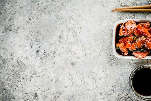 Zalmsashimi in marinade (tamari, sesamolie, citroensap en honing) gegarneerd met zwarte en witte sesamzaadjes