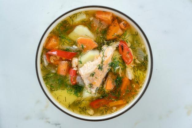 Zalmsoep met aardappelen, wortelen, dille, peper in kom, close-up