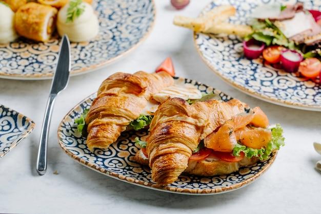 Zalmstukken met sla en tomatenplakken in croissant.