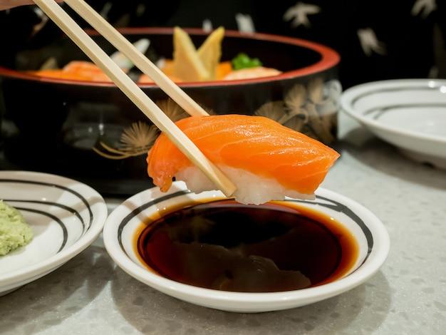 Zalmsushi in eetstokjes die met sojasaus onderdompelen