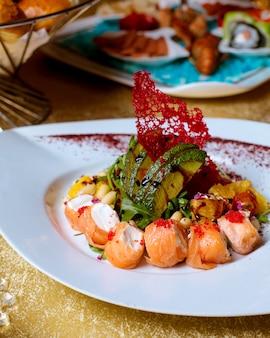 Zalmsushi met groenten worden geplaatst die