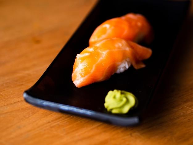 Zalmsushi met wasabi op een zwarte plaat