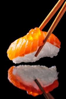 Zalmsushi nigiri in geïsoleerde eetstokjes
