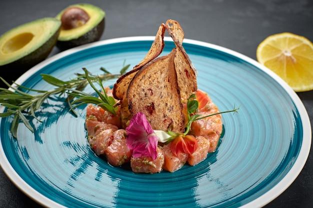 Zalmtartaar met avocado, op een blauw gestreept bord, met limoen en croutons