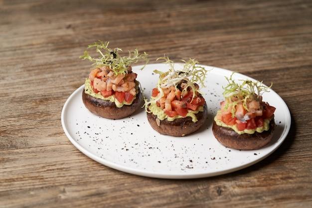 Zalmtartaar met guacamole saus. toosts met guacamole en zalm op witte plaat. luxe restaurantvoedsellijst