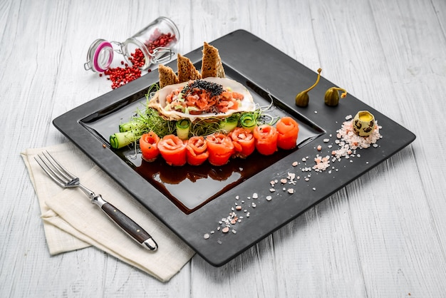Zalmtartaar met verse groenten en toast. op de houten tafel