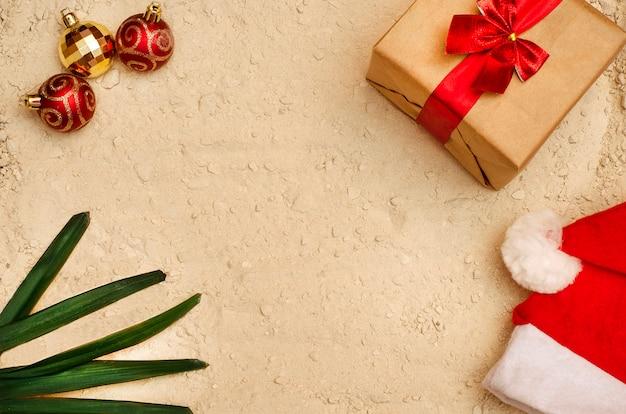 Zand achtergrondstrand voor kerstvakantie. voor reisbureaus. kerstmuts, cadeau, kerstballen en palmbladeren op het zand van een strand.