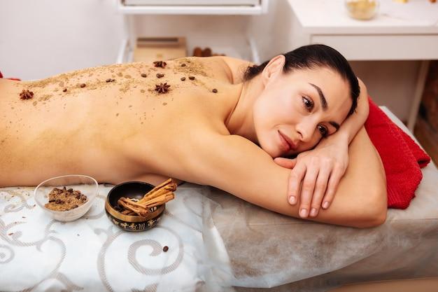 Zand en bonen. doordachte vrouwelijke klant met donkere ogen met speciale kruiden over de blote rug Premium Foto
