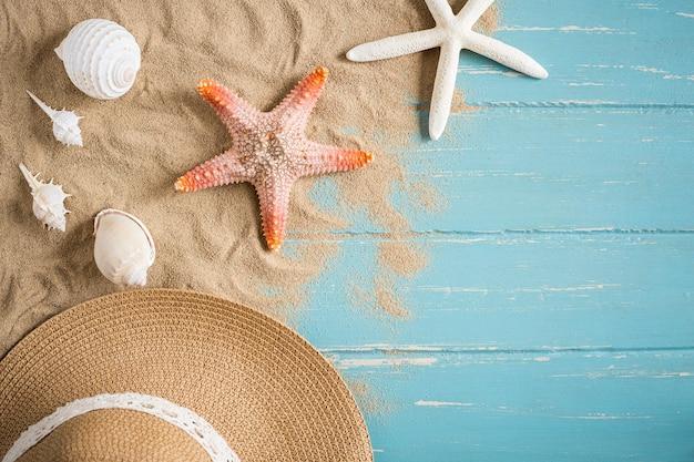 Zand en shells op de houten vloer van het blauwe, de zomerconcept