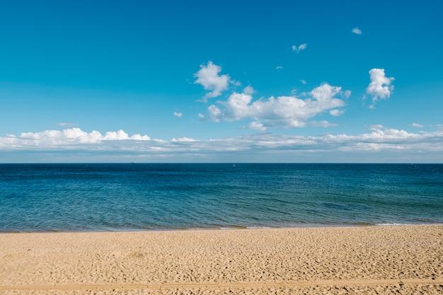 Zand en zee en blauwe hemelachtergrond