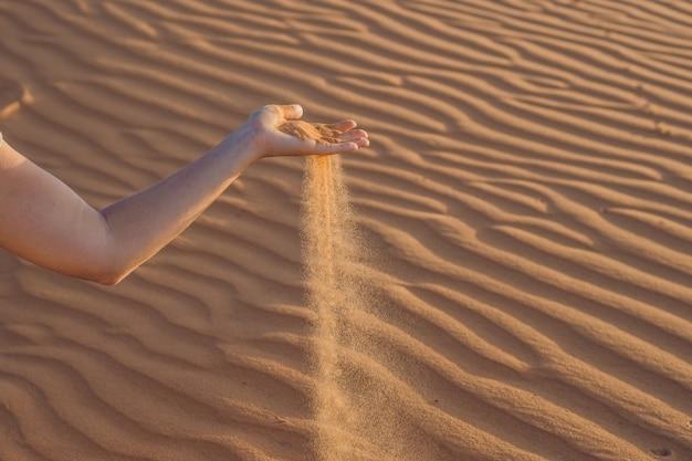 Zand glipt door de vingers van de hand van een vrouw in de woestijn