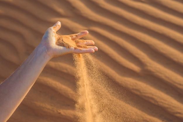 Zand glipt door de vingers van een vrouwenhand in de woestijn.