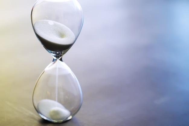 Zand loopt door de bollen van een zandloper die de voorbijgaande tijd meet in een aftelling naar een deadline, op een donkere tafelachtergrond met kopieerruimte.