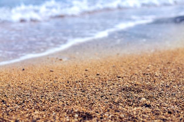 Zand op de oever van de zee. kleine kiezelsteen op het strand van turkije. zee achtergrond. kemer