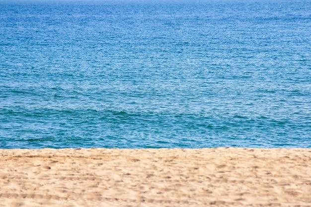 Zand op het strand met blauwe zee op de achtergrond, warme zomerdag