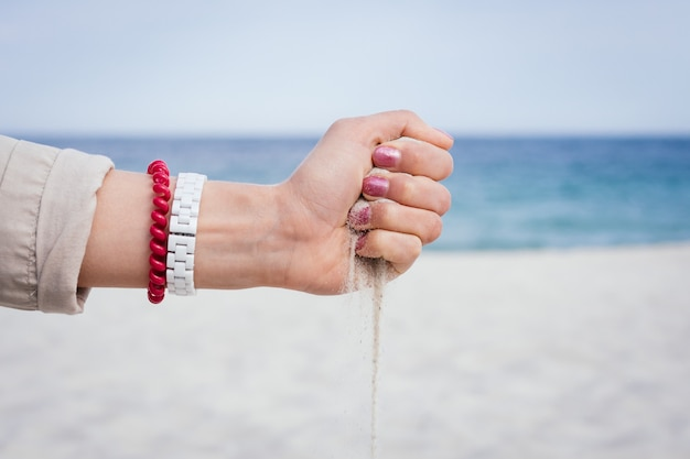 Zand stroomt uit een vrouwelijke hand op het strand