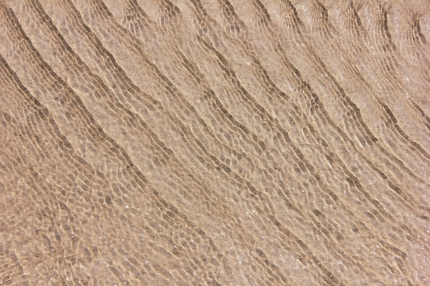 Zandbodem door helder zeewater.