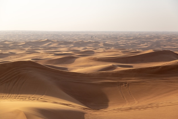 Zandduinen van de woestijn met sporen van autowielen