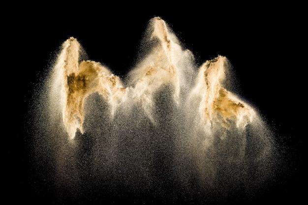 Zandexplosie op zwarte achtergrond wordt geïsoleerd die