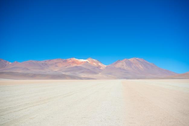 Zandige woestijnstrook en vulkaan op de boliviaanse andes