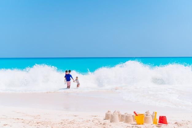 Zandkasteel op wit tropisch strand met plastic kinderspeelgoed
