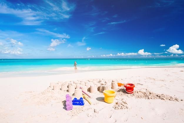 Zandkasteel op wit zandstrand met plastic kinderspeelgoed en zee