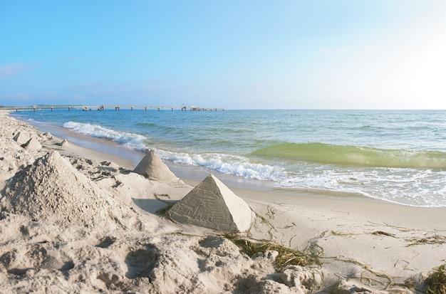 Zandkastelen in de vorm van piramides op een strand aan de oostzee