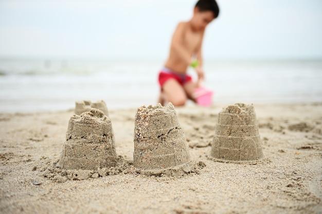 Zandkastelen op de achtergrond van wazige jongen in rode zwembroek tiener bouwt zanderige figuren e