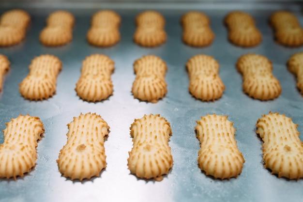 Zandkoek. productie van zandkoekjes in een banketbakkerij. zandkoekjes op een metalen rooster na het bakken in de oven.