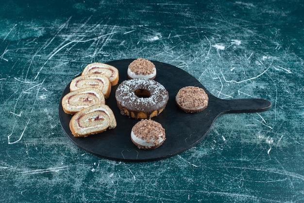 Zandkoekjes, donut en gesneden roll cake op de snijplank op het blauwe oppervlak