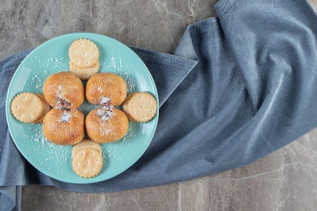 Zandkoekjes en crackers op een bord op een handdoek op marmer.