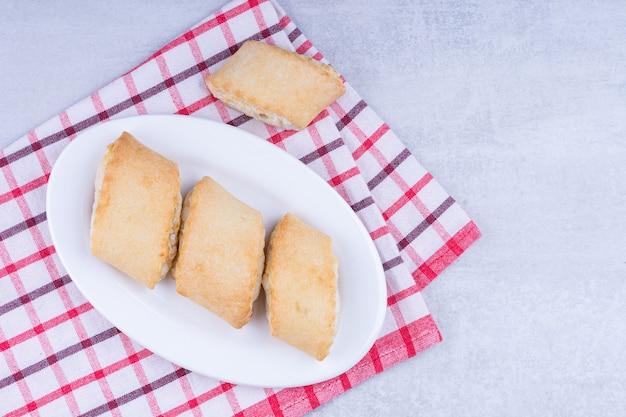 Zandkoekjes op een bord op een theedoek, op het marmer.