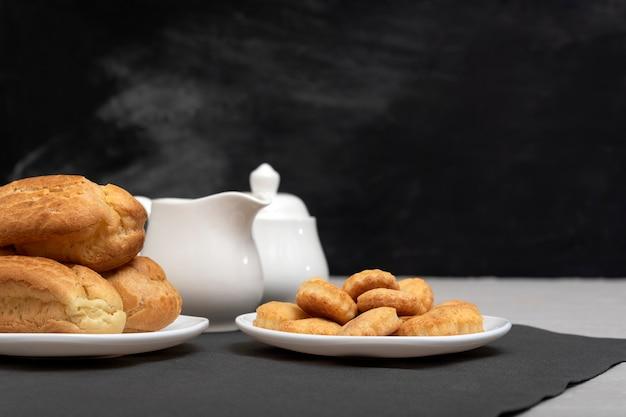 Zandkoekkoekjes en soesjes op tafel in de buurt van hete thee. zelfgemaakt bakken voor thee