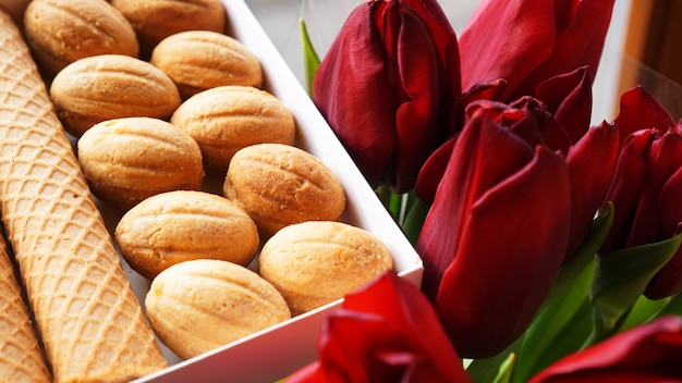 Zandkoekkoekjes en tulpen. cadeau aan de vrouw. russian sweets - oreshki koekjes en tubes