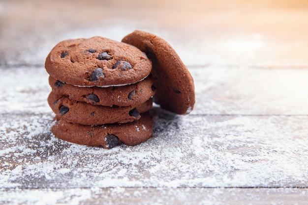 Zandkoekkoekjes met chocoladeschilfers op houten die met poedersuiker worden bestrooid. vers gebak. havermeelkoekjes voor het dessert.