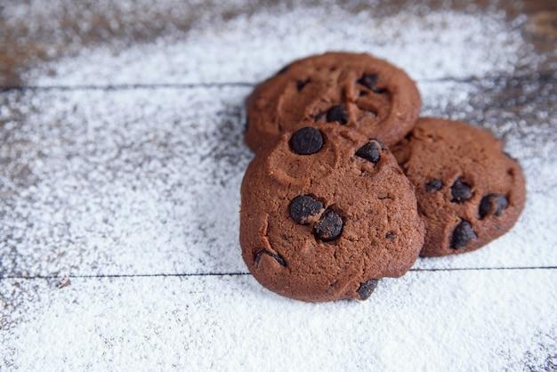 Zandkoekkoekjes met chocoladeschilfers op houten die met poedersuiker worden bestrooid. vers gebak. havermoutkoekjes voor ontbijt. bovenaanzicht